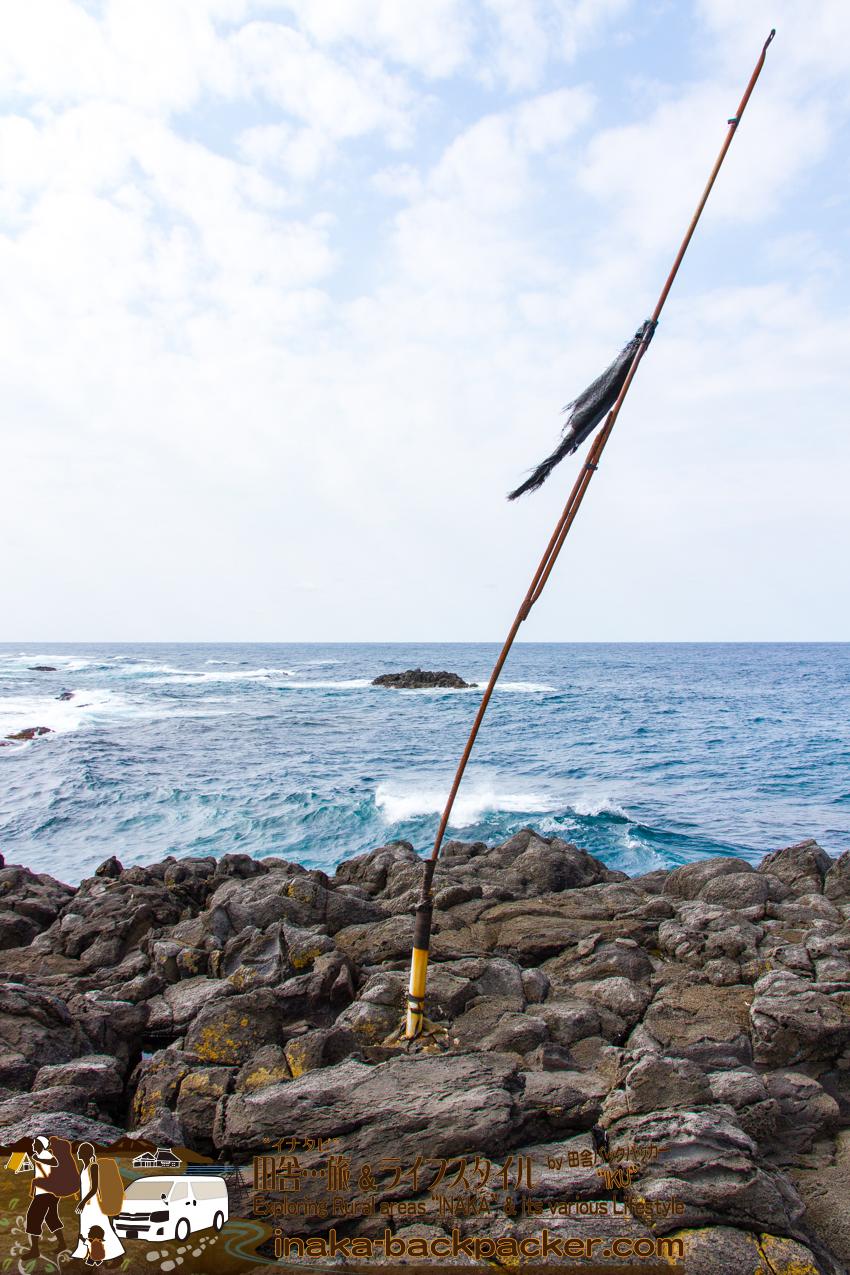 舳倉島の海岸にたつ旗。何の旗だかわからない状態になっていた。