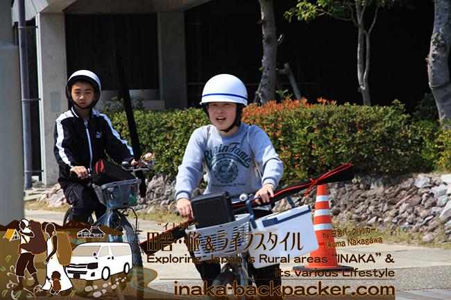 """熊本県天草市牛深 – 自転車のかごに釣竿を入れて、「うしぶか海彩館」にやってきた中学生たち。対自然との遊びがごく""""普通""""の子どもたち"""