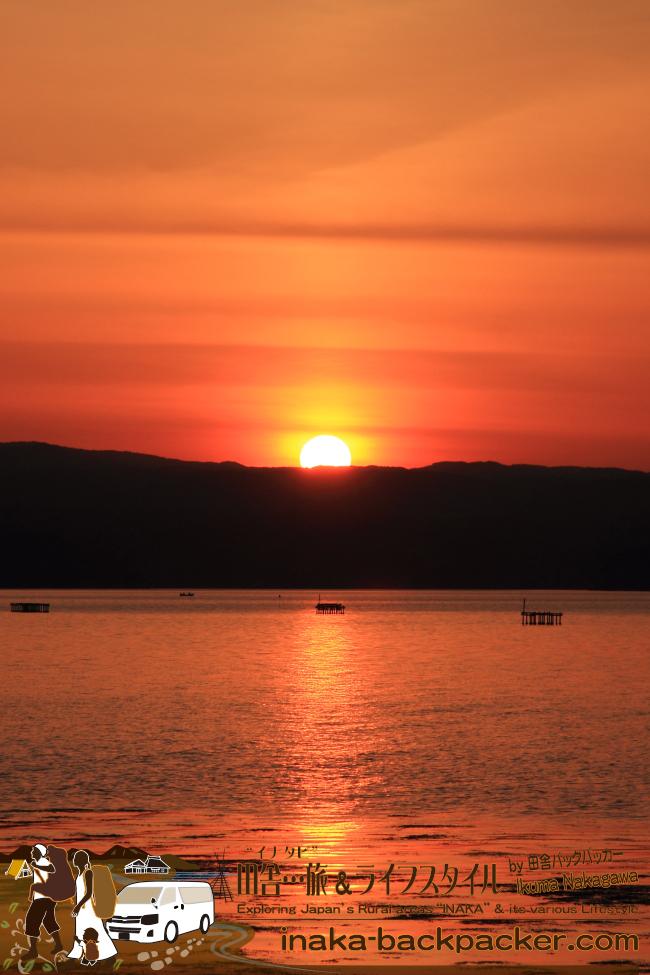 """能登・穴水町岩車 – 夕日を撮るために海の中へ。""""中""""と言っても、海は湖のように穏やかで波がない。ちょっと外へ出れば自然を身近で体感できる""""能登の里山里海""""の田舎…いいよねぇ"""