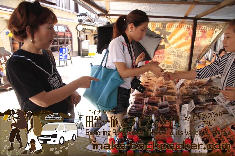 能登・輪島市 - 朝市で。伊豆田さん宅にホームステイしている韓国のジュアがイカの干し物をライターで炙って試食。