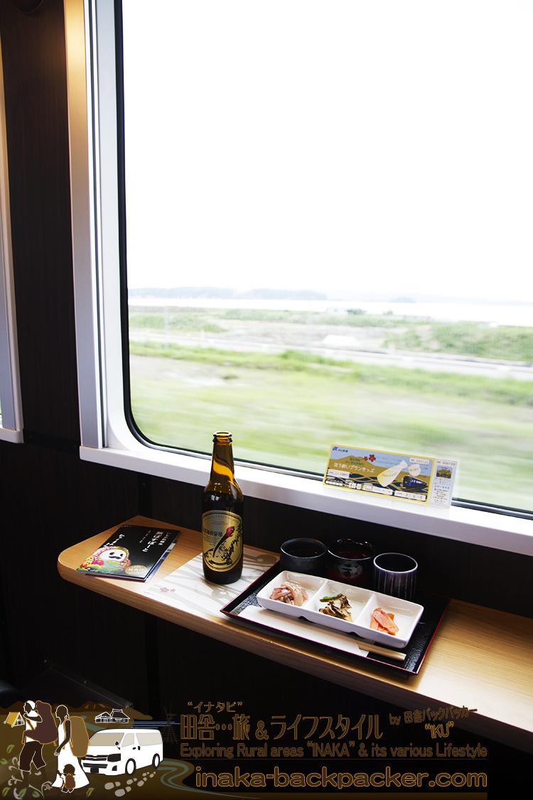 """のと里山里海号の「ほろ酔いプラン」のセット。地酒のコップには能登島ガラス、珠洲焼などのコップを活用。コップは深く、お酒の量は意外と多く、飲み干すごろには""""ほろ酔い""""気分に..."""