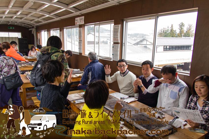 """能登・穴水町(石川県) - """"おもしろい""""牡蠣食堂。穴水駅の跨線橋の通路上で、これから牡蠣を食べる。「みんな、注文は決まった?」"""