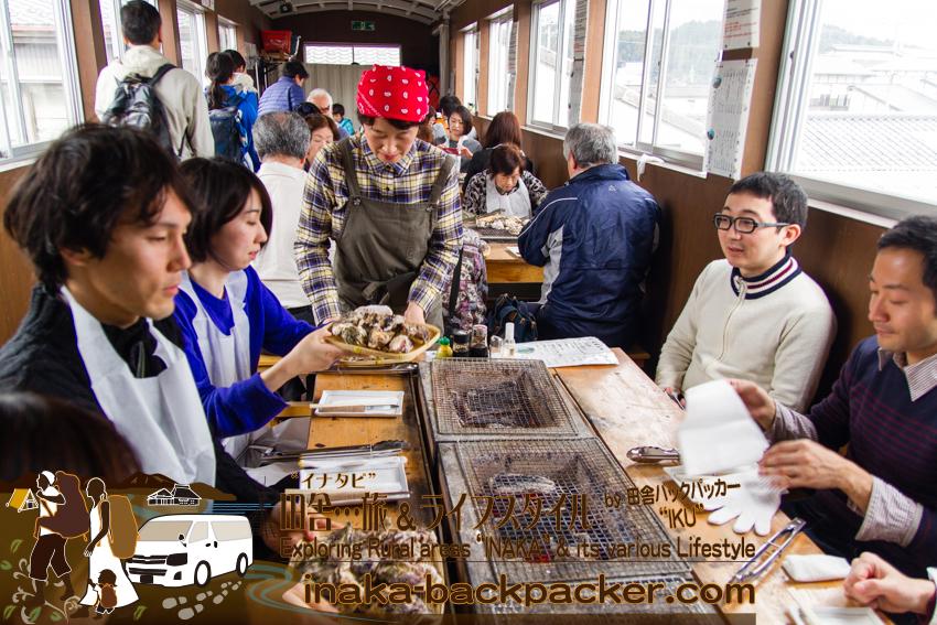 能登・穴水町(石川県) - 穴水駅の跨線橋の通路は、牡蠣を食べるグループで一杯になっている。穴水町のユニークな牡蠣食堂「穴水駅ホームあつあつ亭」。