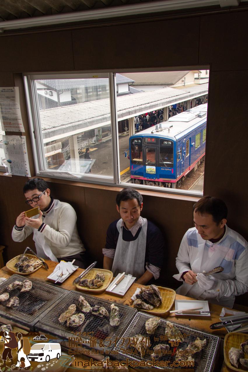 穴水駅「穴水駅ホームあつあつ亭」の跨線橋の通路上という、かなりユニークな場所で牡蠣を食べる。