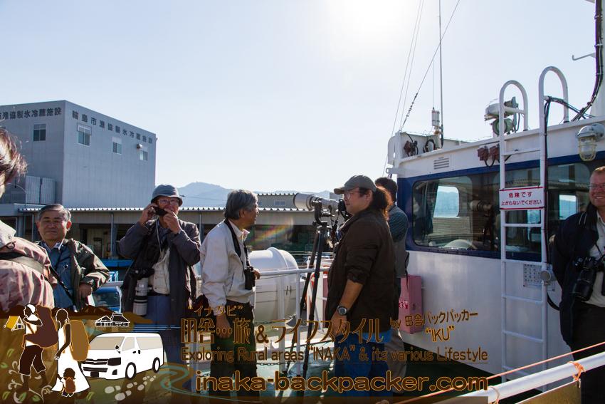 能登・舳倉島への定期船に乗っている多くの野鳥カメラマン。カメラに100万円以上かけている。趣味でカメラをしている人たちが多いそうだ。Bird watchers, on a ship to Hegura Island, are carrying SLR and its US$12,000 lens. Most of them take photos for fun, as their hobby.